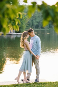 Cute couple in love, closing their eyes and touching their foreheads while walking near the lake