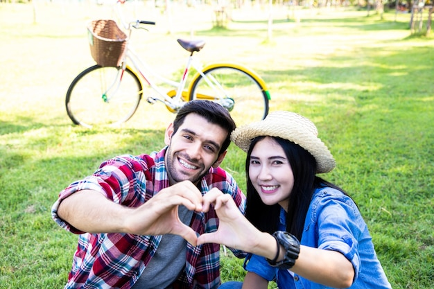 Cute of couple love making heart shape with hands and bright smile in public park they rest after exercise by going for a bike ride