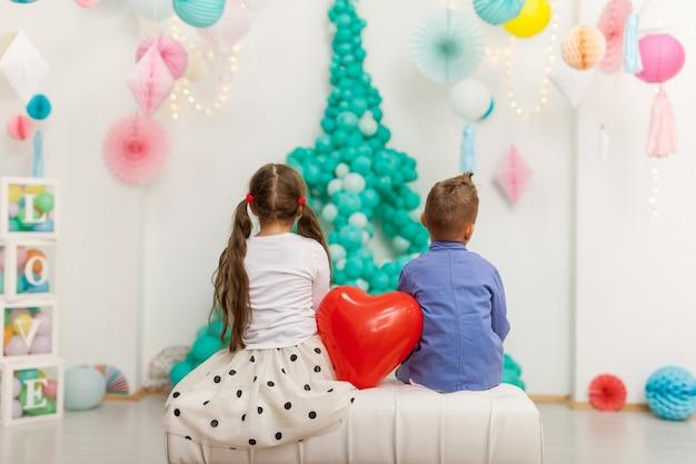 레드 하트 풍선과 함께 아이의 귀여운 커플입니다. 발렌타인 데이 및 사랑 개념, 스튜디오 촬영