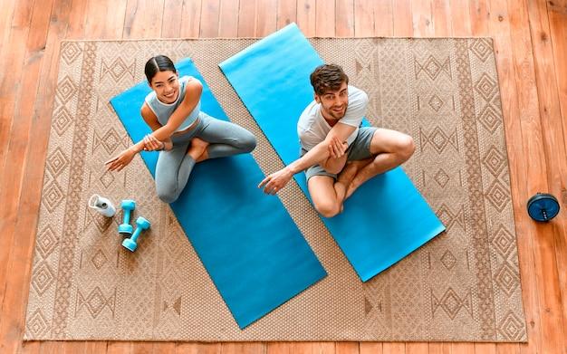 Милая пара корейской женщины и мускулистого мужчины в спортивной одежде делают упражнения в гостиной дома. здоровый образ жизни, спорт, йога, фитнес. вид сверху.