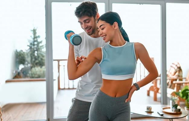 Милая пара корейской женщины и мускулистого мужчины в спортивной одежде делают упражнения с гантелями в гостиной дома. здоровый образ жизни, спорт, йога, фитнес.
