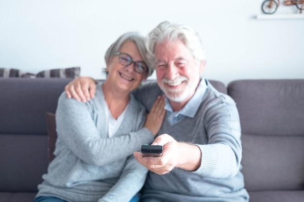 Симпатичная пара из двух зрелых пожилых людей кавказа на диване, смотрящем фильм или что-то в телевизоре - мужчина держит пульт