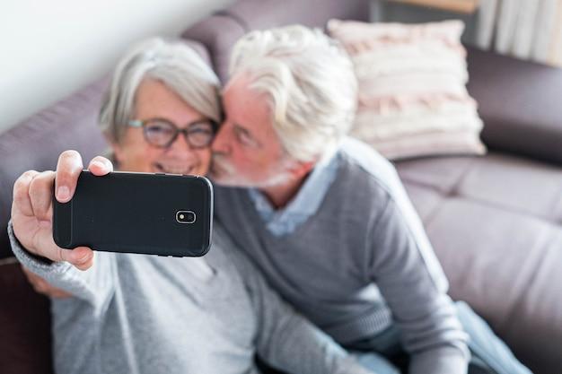 두 노인의 귀여운 커플은 집에 있는 소파에 함께 앉아 셀카를 찍고 결혼했습니다 - 성숙한 남자는 아내가 사진을 찍는 동안 아내에게 키스를 합니다