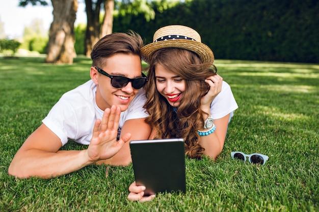 Милая пара молодых людей лежит на траве в летнем парке. девушка в шляпе с длинными вьющимися волосами держит планшет, у них хорошее настроение и общение на планшете.