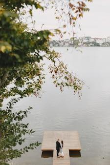 Coppia carina in un parco. signora in un cappotto grigio. persone sul molo.
