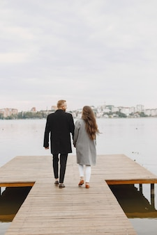 Cute couple in a park. lady in a gray coat. people on the pier.