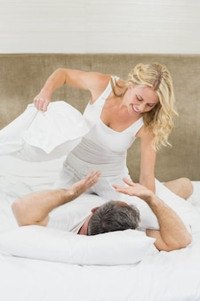 Cute couple playing pillow fight in bed