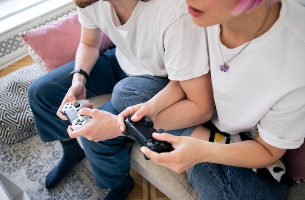 Милая пара играет в видеоигры на диване
