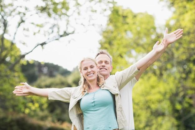 Cute couple raising arms outside