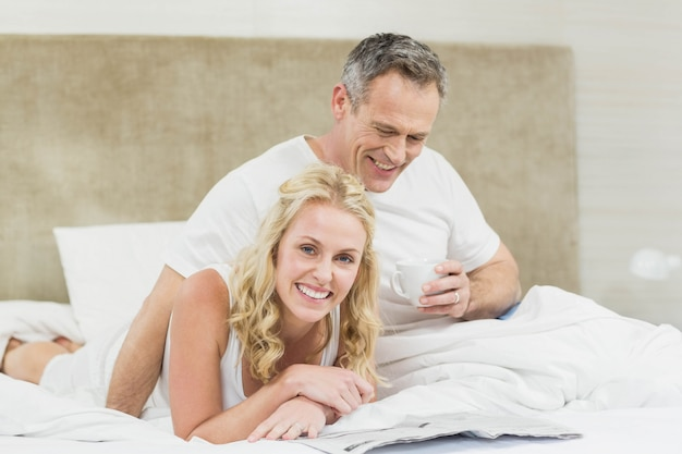 Cute couple reading the news in their room