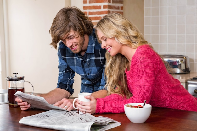 Cute couple reading the newspaper in the kitchen