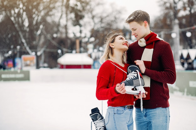 Cute couple in a red sweaters having fun in a ice arena