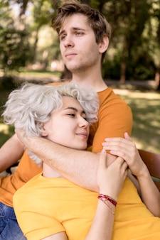 かわいいカップルが公園にいる間ベンチで一緒にリラックス