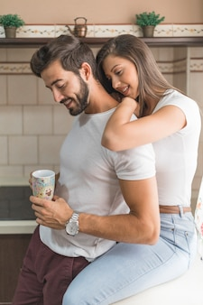 Cute couple resting in kitchen in morning