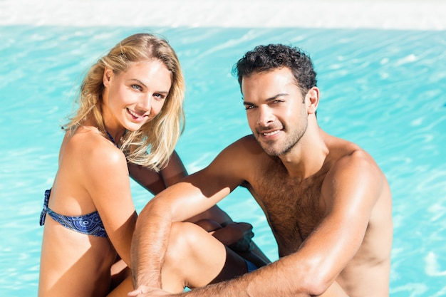 Cute couple sitting on the edge of the pool