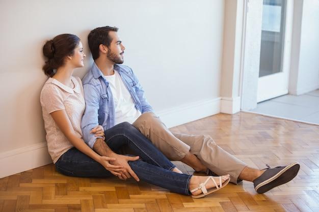 かわいいカップルは、壁に床に座って