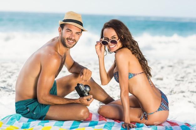 ビーチに座っているかわいいカップル