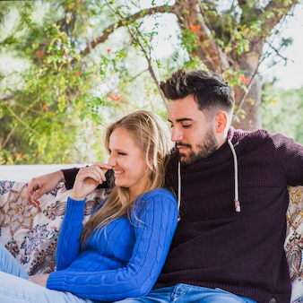 Cute couple sitting on sofa near greenery