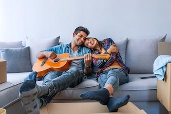 かわいいカップルが彼らの新しい家で開梱から休憩を取って