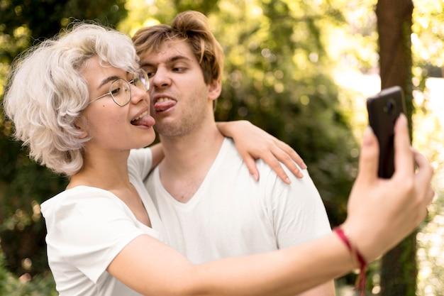 かわいいカップル、selfieを取り、醜い顔を作る