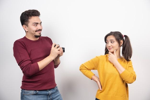카메라로 사진을 찍고 흰 벽 위에 포즈를 취하는 귀여운 커플.