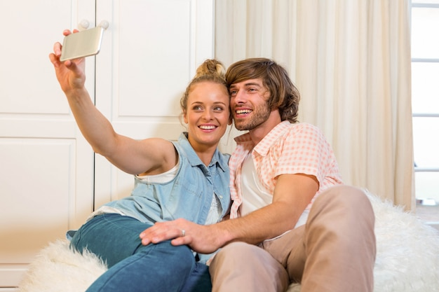 Cute couple taking a selfie with smartphone in the living room