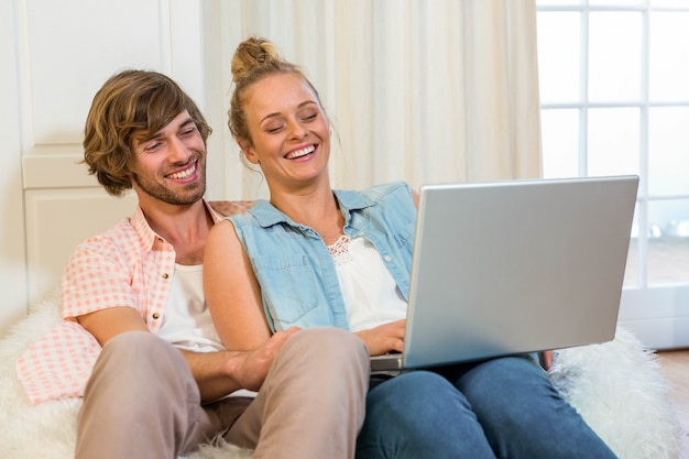 Cute couple using laptop sitting on the couch in the living room