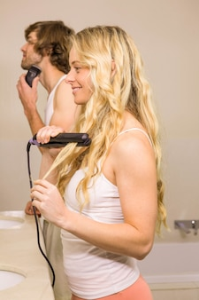 Cute couple using a razor and a straightener in the bathroom at home