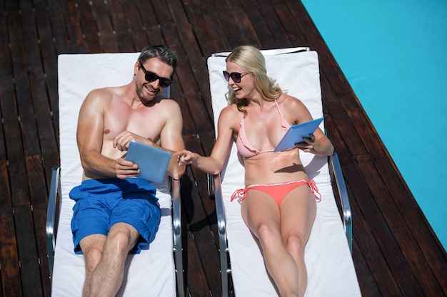 Милая пара с помощью планшета и лежа на шезлонгах