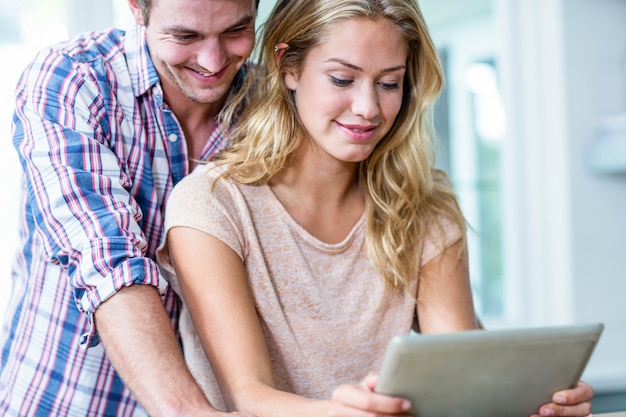 Cute couple using tablet computer in the kitchen at home