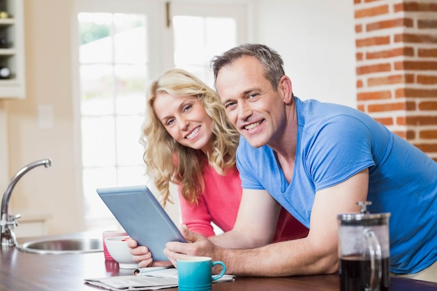 Cute couple using tablet in the kitchen