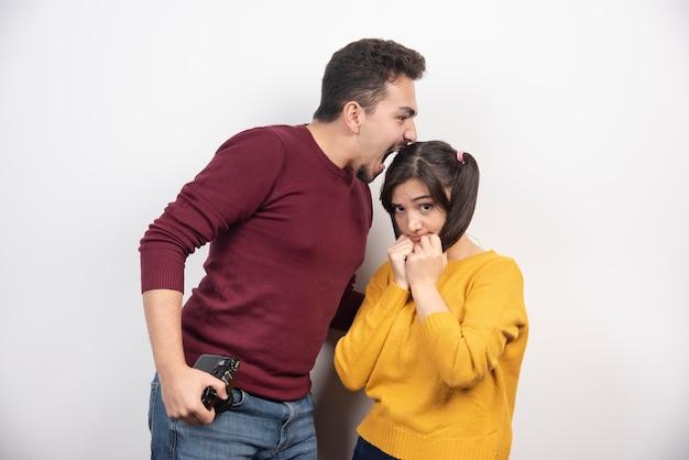 흰 벽 위에 포즈를 취하는 카메라와 함께 귀여운 커플.