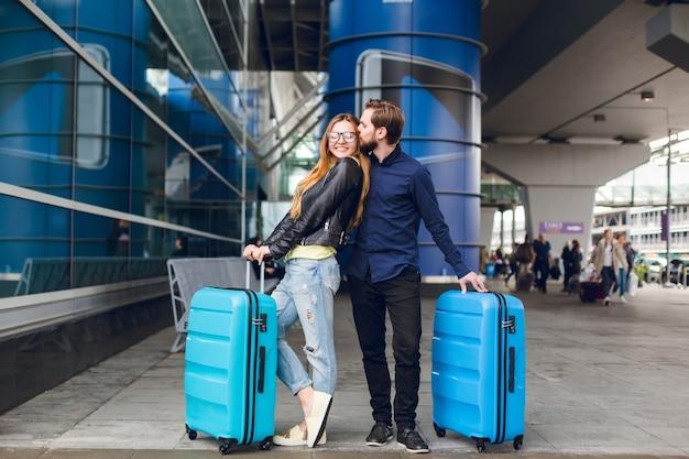 スーツケースとかわいいカップルが空港の外に立っています。彼女は長い髪、メガネ、黄色いセーター、ジャケットを持っています。彼は黒いシャツ、ひげを着ています。男は女の子を抱き合ってキスしています。