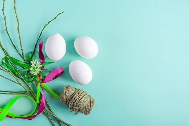 흰색 달걀, 버드 나무 어린 가지와 녹색 바탕에 화려한 리본 귀여운 창조적 인 부활절 구성. diy 및 어린이 창의력. 수제 공예. 인사말 카드, 모의. 텍스트를위한 공간 복사