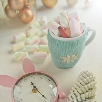 Симпатичная чашка, украшенная розовым зефиром и розовыми часами, рождественскими украшениями. время до вечеринки. вкусные сладости и кружка с корицей и конфетами.