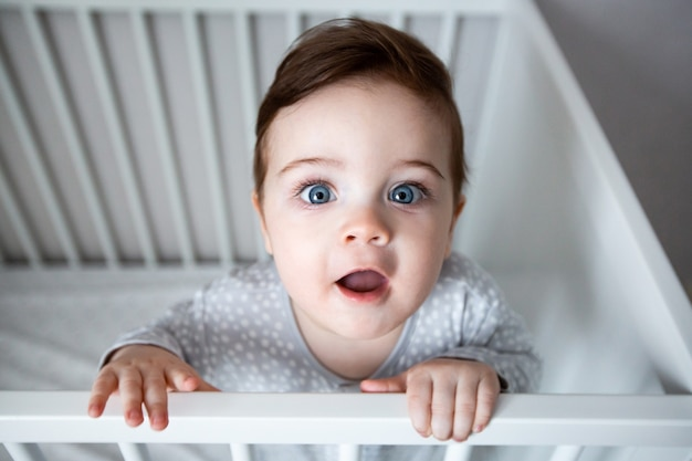 Cute curious baby standing in a white crib bed.