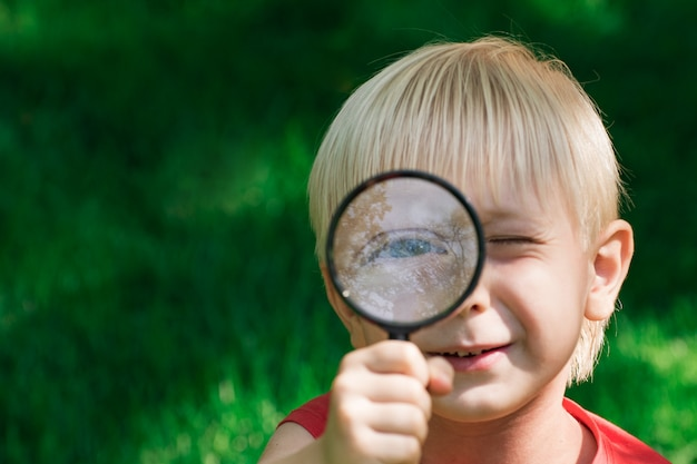 Cute curious child looking through a magnifying glass. serious boy exploring the environment.