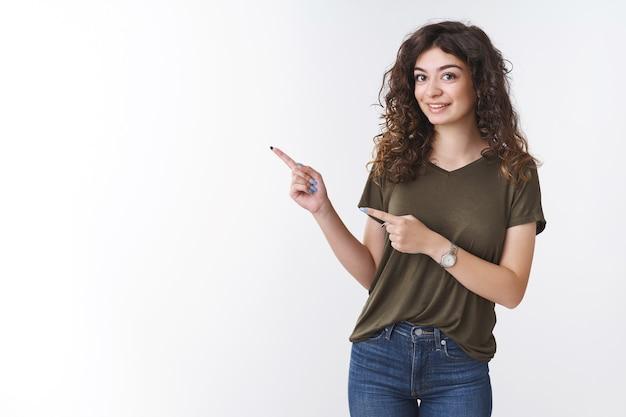 かわいい好奇心旺盛なガールフレンドが質問をしているところに興味のある左を指しているのは人差し指が興味をそそられて興奮して立っている白い背景をもっと近くで見たいと思っていることを示しています