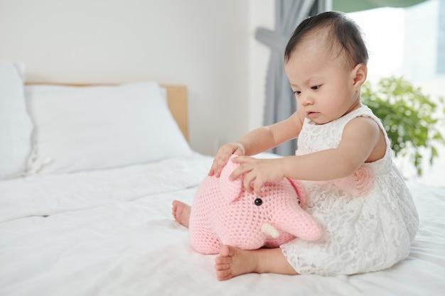귀여운 호기심 어린 아시아 소녀가 침대에 앉아 박제 동물을 가지고 노는