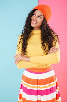 Cute curly african young woman in hat standing with arms crossed and thinking