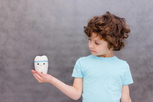 Симпатичный кудрявый мальчик держит большой зуб и удивлен на серой стене. мальчик потерял первый молочный зуб. концепция здоровых зубов, стоматологическая клиника.