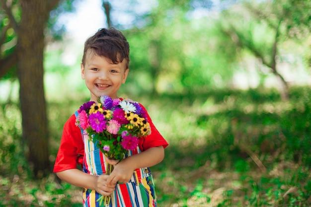 花の花束を持つかわいい巻き毛の少年明るい野生の花と赤いtシャツの子供