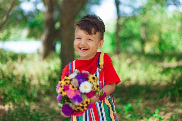 Cute curly boy with a bouquet of flowers a child in a red tshirt with bright wildflowers in nature i...