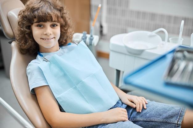 치과 병원에서 치과 의사를 기다리는 동안 웃는 귀여운 곱슬 아이