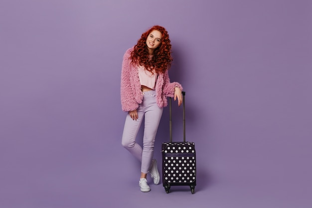 Cute curly girl in pink top leaned on suitcase. portrait of redhead woman wearing wool jacket.