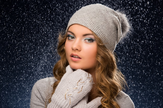 Cute curly girl wearing mittens during snowfall