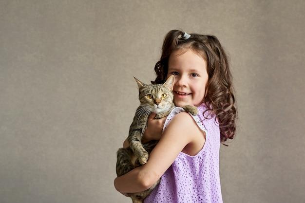 灰色の背景に彼女の腕の中で猫とかわいい巻き毛の女の子