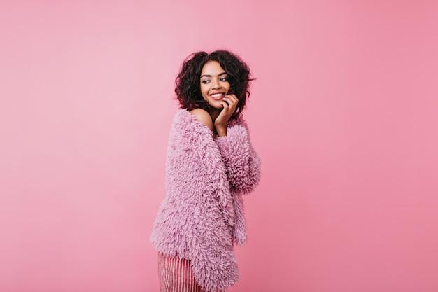 짧은 머리를 가진 귀엽고 곱슬 머리 소녀는 모피 코트에서 편안함을 느낍니다. 분홍색 옷을 입고 웃는 아가씨의 사진.