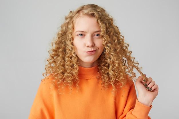 Симпатичная кудрявая блондинка с голубыми глазами, подозрительно смотрящая вперед, держит прядь волос, думая о чем-то