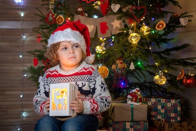 クリスマスツリーで赤いサンタの帽子をかぶったかわいい縮れ毛の少年。クリスマスと新年のコンセプト